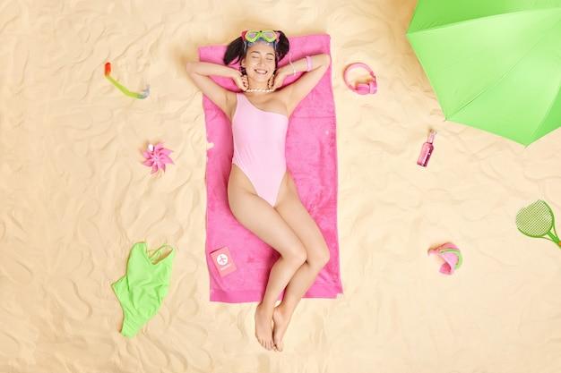 여자는 필요한 액세서리로 둘러싸인 해수욕복을 입고 다이빙한 후 모래 해변에서 분홍색 수건에 선탠을 하고 스노클링 마스크를 착용합니다. 완벽한 휴가