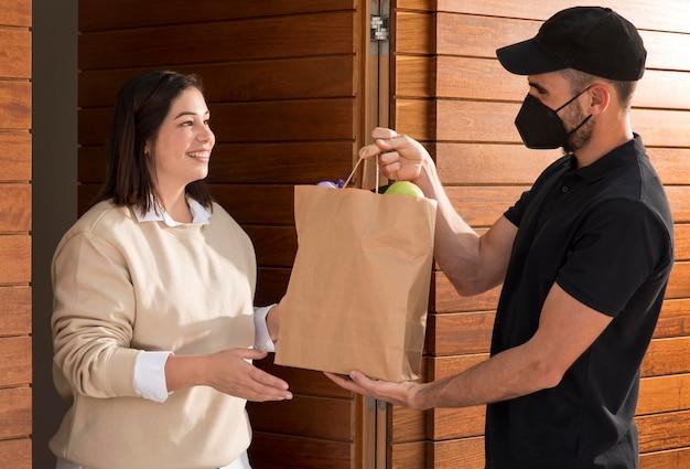 배달 된 음식 가방을받는 여자