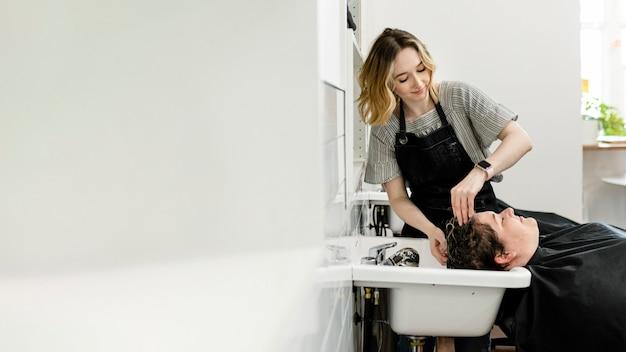 Женщина моет волосы в салоне красоты