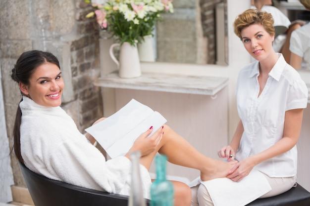 美容師からペディキュアを得ている女性