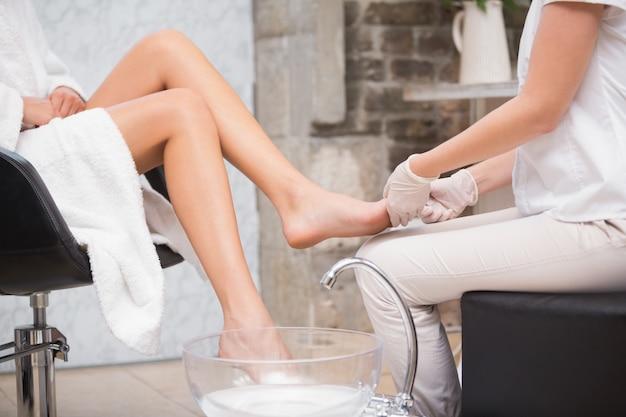 Женщина получает педикюр от косметолога