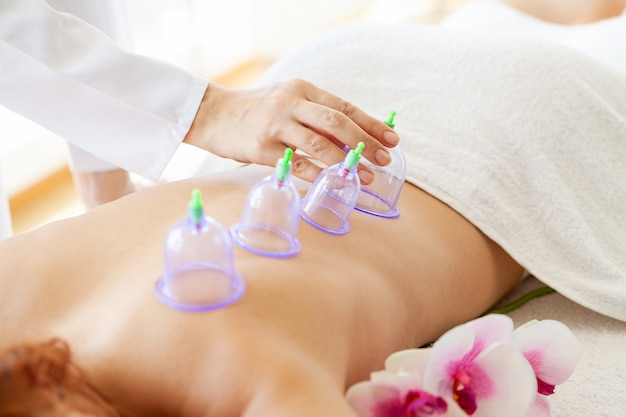 Woman getting anti-cellulite massage of back with use of vacuum cans in beauty studio