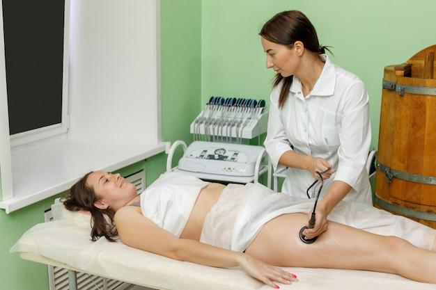 Женщина получает антицеллюлитную терапию в салоне красоты