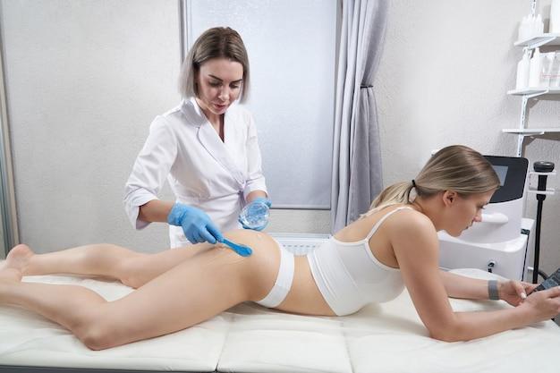 ビューティーサロンハードウェア美容ボディケアスパでアンチセルライトとアンチファットセラピーを受けている女性