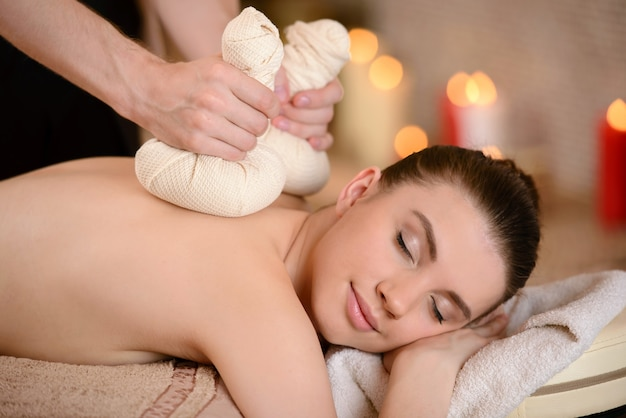 Woman getting a back massage with herbal compresses.