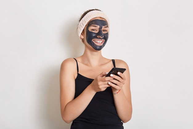 Woman getting black facial mask, holding small mirror in hands, wearing hair band and sleeveless t shirt