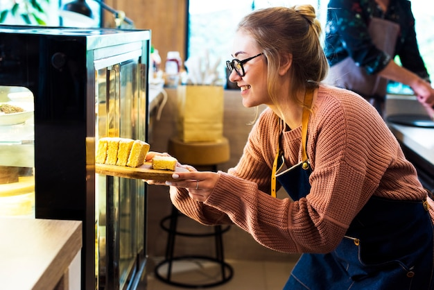 디스플레이 냉장고에서 케이크를 받고 여자