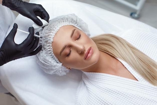 여자 뺨, 근접 촬영에에서 보톡스의 화장품 주입을 받고. 뷰티 살롱에서 여자입니다. 성형 외과.