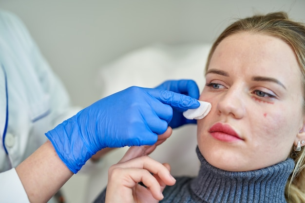 Женщина получает косметическую инъекцию ботокса возле глаз, крупным планом