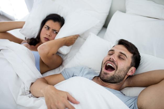 여자는 침실에서 침대에 코골이 남자와 방해 받고