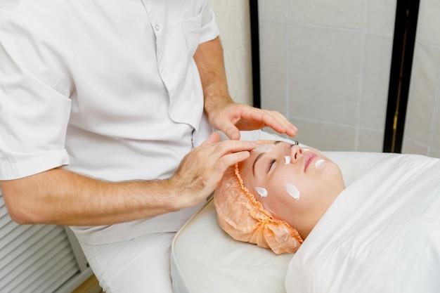 Женщина получает массаж лица. санаторно-курортное лечение в салоне красоты