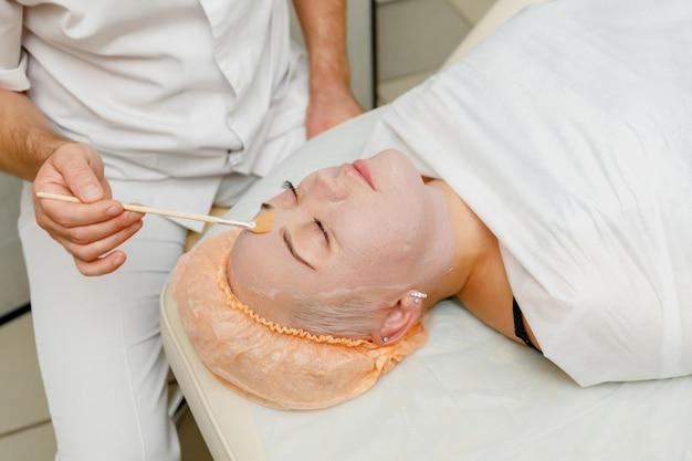 Женщина получает пилинг-маску для лица в салоне красоты