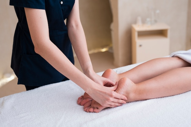 Woman getting feet massage at spa