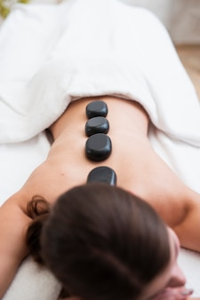 Woman getting heated rocks on back at spa
