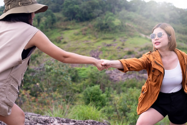 Woman getting help from a friend to climb a rock