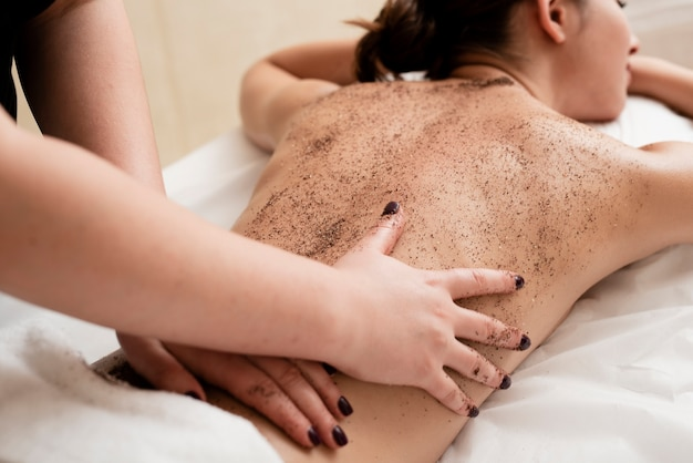 Woman getting her back exfoliated at spa