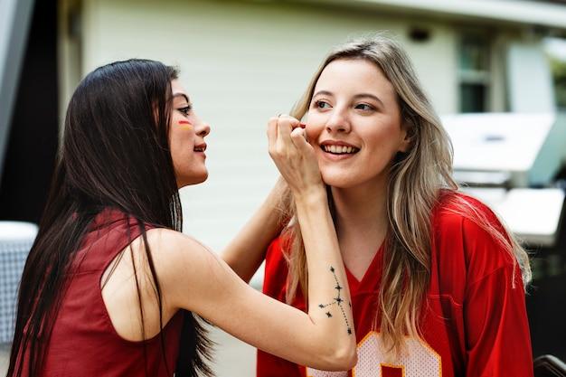 チームカラーで頬を塗る女性
