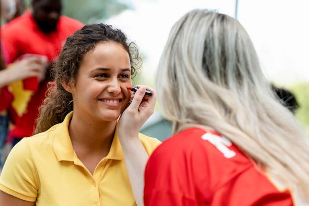 그녀의 뺨을 팀 색상으로 칠하는 여성