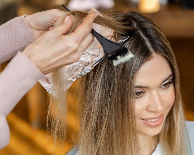 Женщина красит волосы дома парикмахером