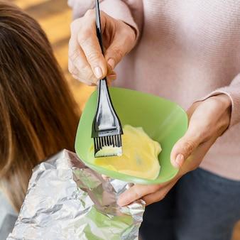 家で髪を染める女性