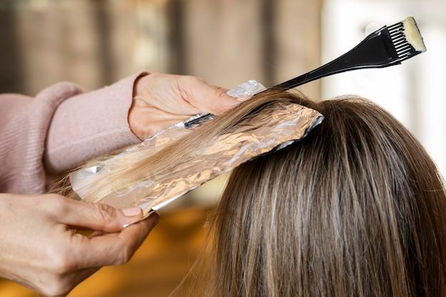 自宅でヘアスタイリストに髪を染めてもらう女性