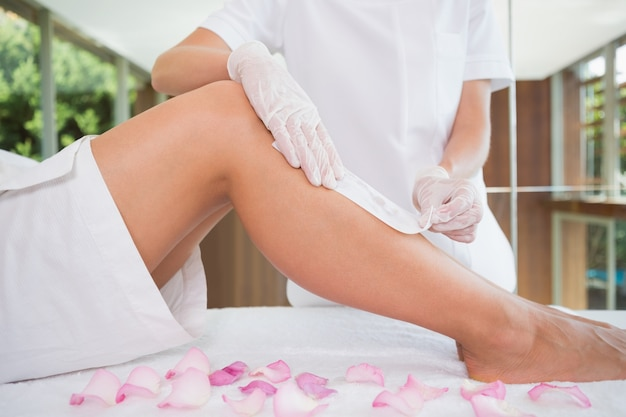 Woman getting her legs waxed by beauty therapist