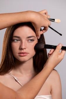 Женщина делает макияж, сделанный профессионалом