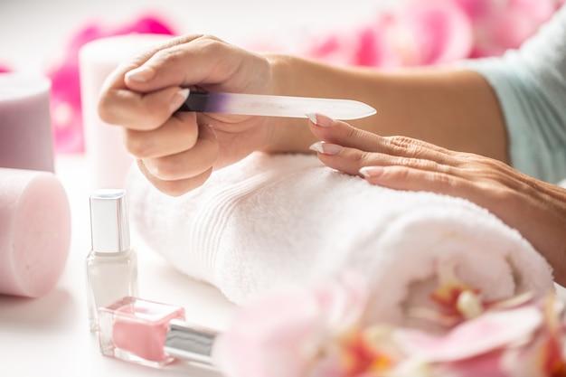 Женщина делает ей ногти пилкой и набором лаков в салоне.