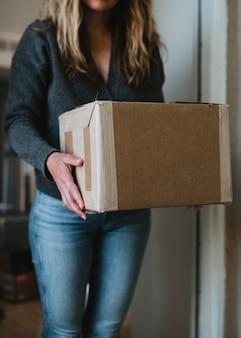 コロナウイルスのパンデミックの間に正面玄関から彼女のパッケージを取得する女性