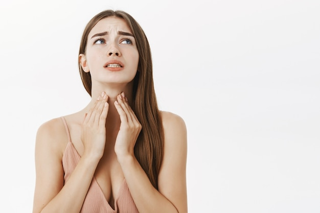 Женщина заболела перед важной встречей, чувствуя дискомфорт и страдая от боли в горле, касаясь шеи, хмурясь и стиснув зубы от ужасного чувства, позирует