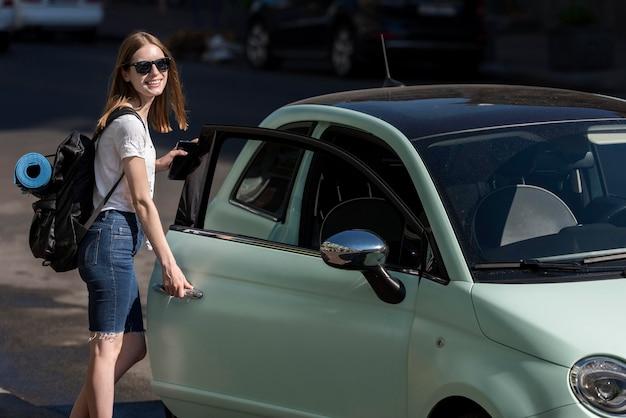 Женщина садится в машину для путешествия