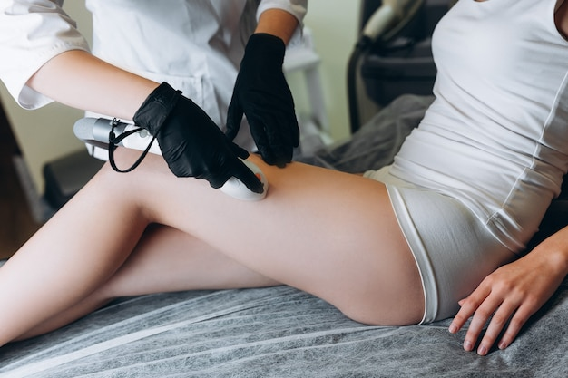 Woman getting laser treatment on her legs in a beauty salon. cosmetologist doing laser epilation to her client.