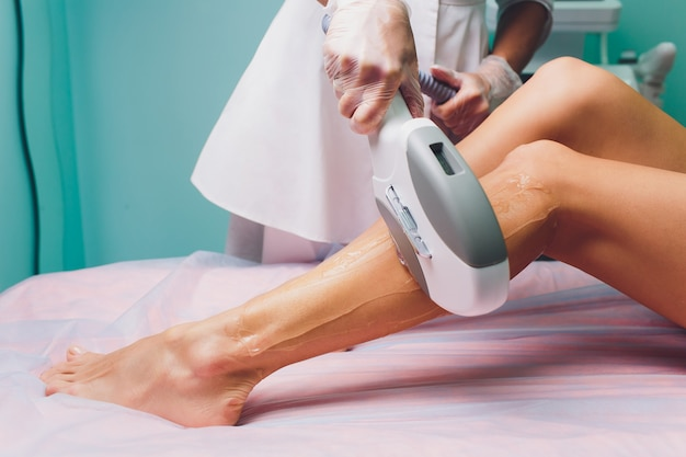 Woman getting laser treatment in medical spa center, permanent hair removal concept.