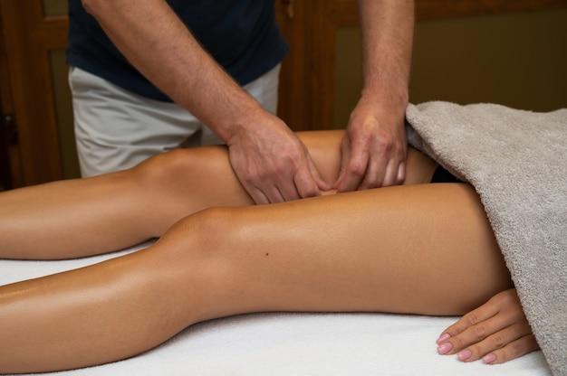 Женщина получает лимфодренажный массаж ног в спа-салоне. крупный план. красота релаксации тела и концепция ухода за телом.