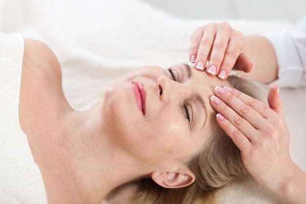 Женщина получает массаж лица и шеи в спа-салоне