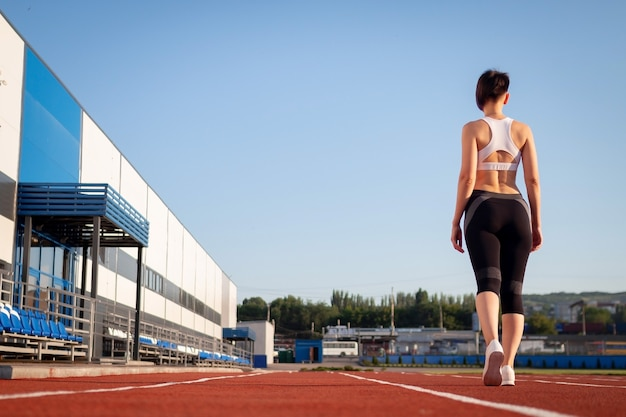 Woman getting ready to start on stadium, summer outdoors training. woman run training outdoors. health and sport concept.