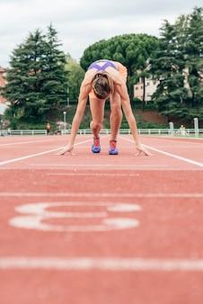 경기장에서 달리기 시작할 준비를 하는 여성