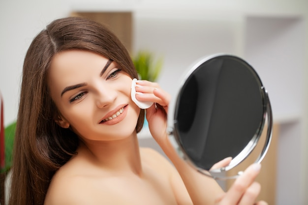 Woman getting ready for work doing morning makeup in bathroom mirror at home