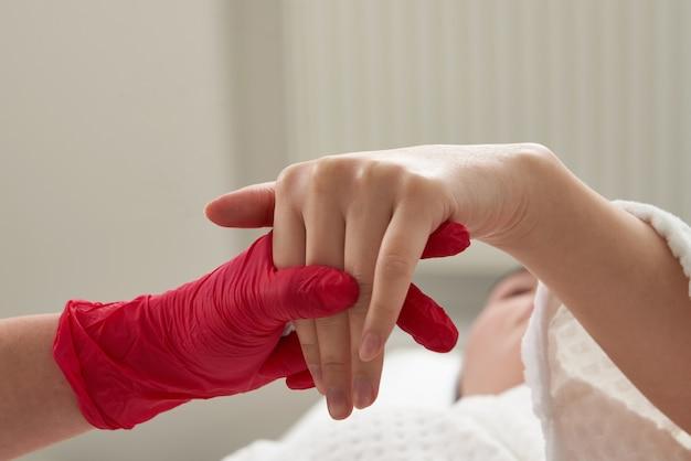Женщина получает инъекции омолаживающего наполнителя в руке. косметолог, вводя наполнитель в кожу рук