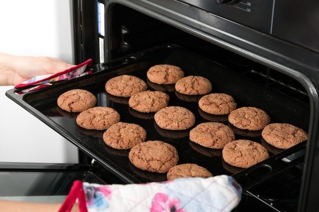 オーブンからオート麦クッキーでローストパンを得る女性