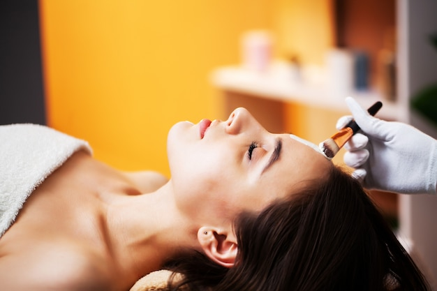 Woman getting spa face mask in beauty center