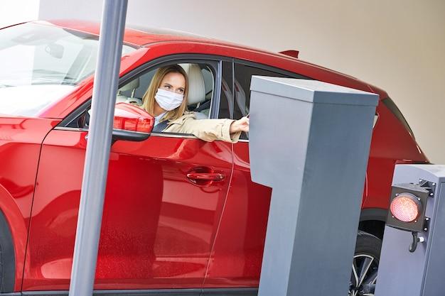 Женщина получает билет от паркомата на подземной парковке
