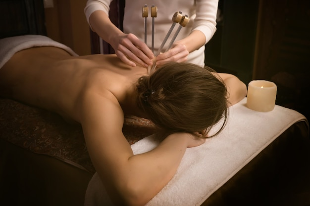 Acutonicリラックスマッサージとサウンドヒーリングによってスパで治療を受けている女性