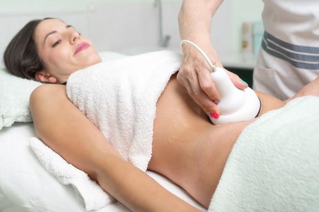 Женщина получает лечение кавитации ультразвуком у клиента-косметолога, наслаждаясь антицеллюлитом ...