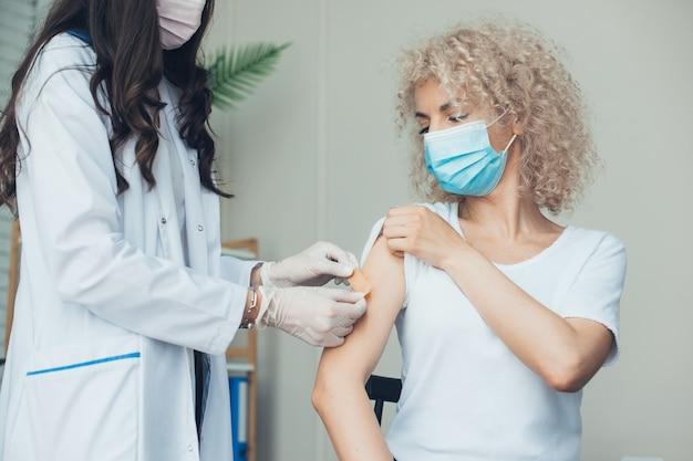 예방 접종을 받는 여자 백신을 갖춘 간호사의 보호를 받는 행복한 소녀