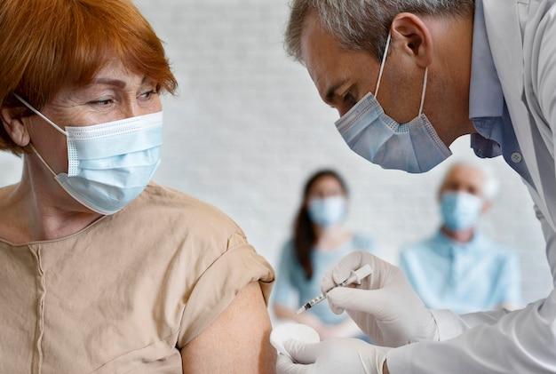 Женщина получает вакцину от мужчины-медика
