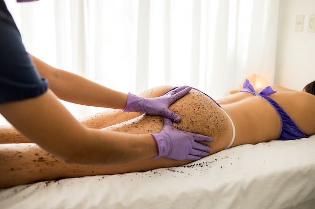 Woman getting a whole-body relaxing scrub massage done in a spa