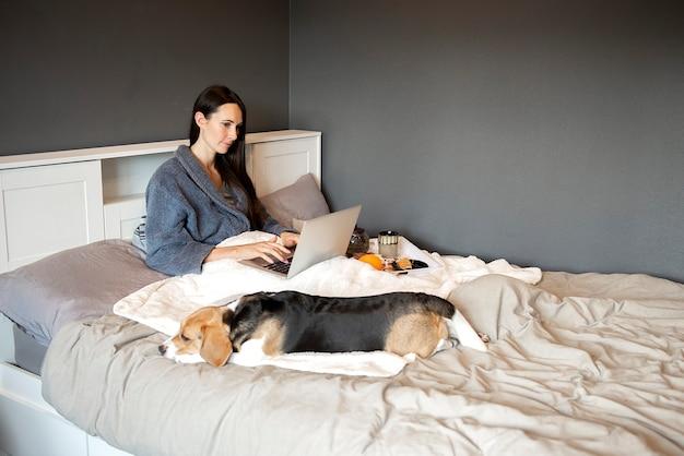 Женщина, девушка и собака наслаждаются чаем и завтраком в постели, работая на ноутбуке