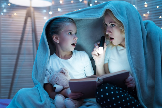 Woman and girl are reading book with flashlight
