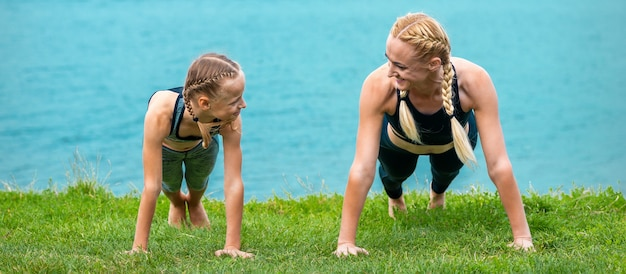 Woman and girl doing push-up exercise on the grass near lake outdoors